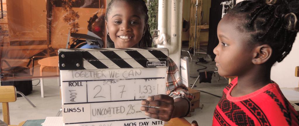 Girl holds up film slate