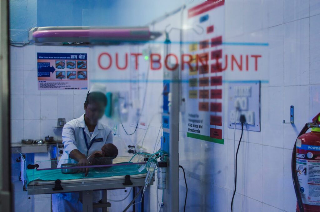 A doctor holding a baby born prematurely in an incubator.
