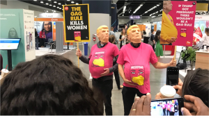 """The Women Deliver conference witnessed an ad-hoc protest. Two people wearing Donald Trump masks and pink t-shirts with a 'resist gag' logo hold signs saying """"The gag rule kills women"""" and """"If Trump got pregnant there wouldn't be a gag rule""""."""