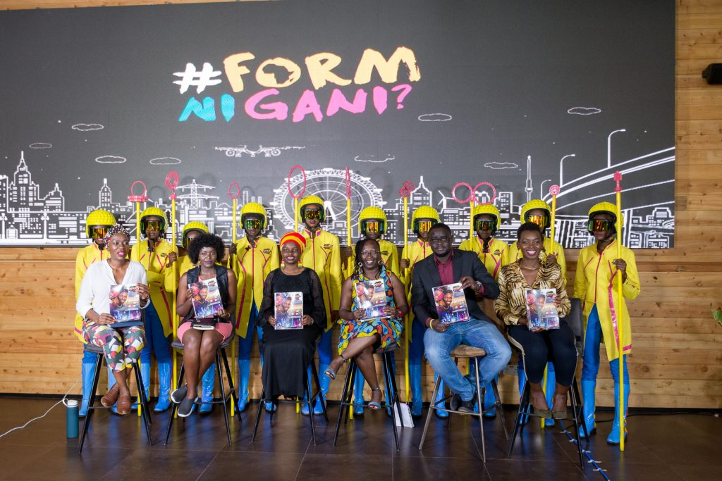 #formnigani movement's Futures Report launch. A group of people sit on chairs holding the report in their hands. Behind them is the futuristic guard of Kenya's 2063 president in their yellow helmets and jackets and bright blue trousers.