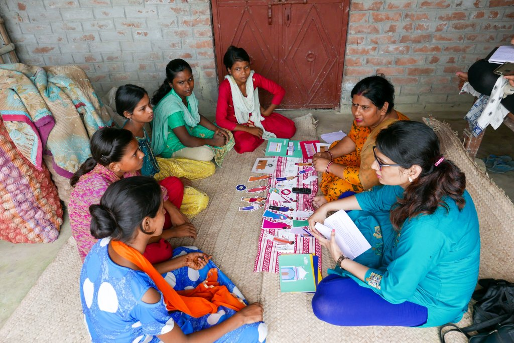 Indian women sitting in a circle during a design research engagement. In the middle are different design tools used to guide the conversation.