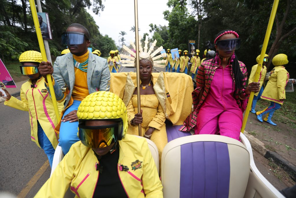 The future queen of Kenya travelling on a convertible car in her yellow robe and golden crown, surrounded by her aides wearing all yellow outfits.