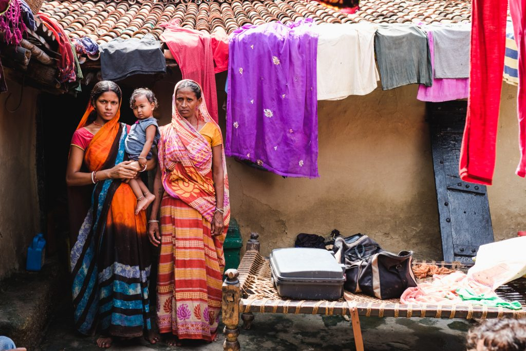 A pregnant woman, her toddler, and her mother are standing in front of their house in an informal settlement. Colourful clothing is left to dry on the roof. They are preparing to pack for the hospital for the pregnant woman to give birth..