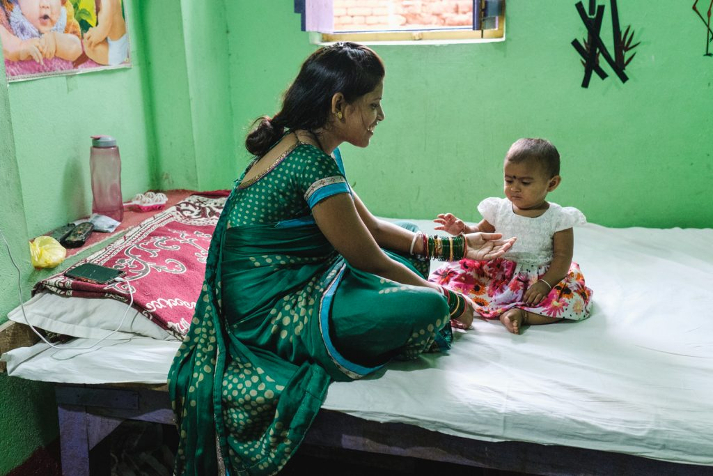A woman is playing with her toddler on a hospital bed. Being able to receive antenatal and postnatal care is important for reproductive health.