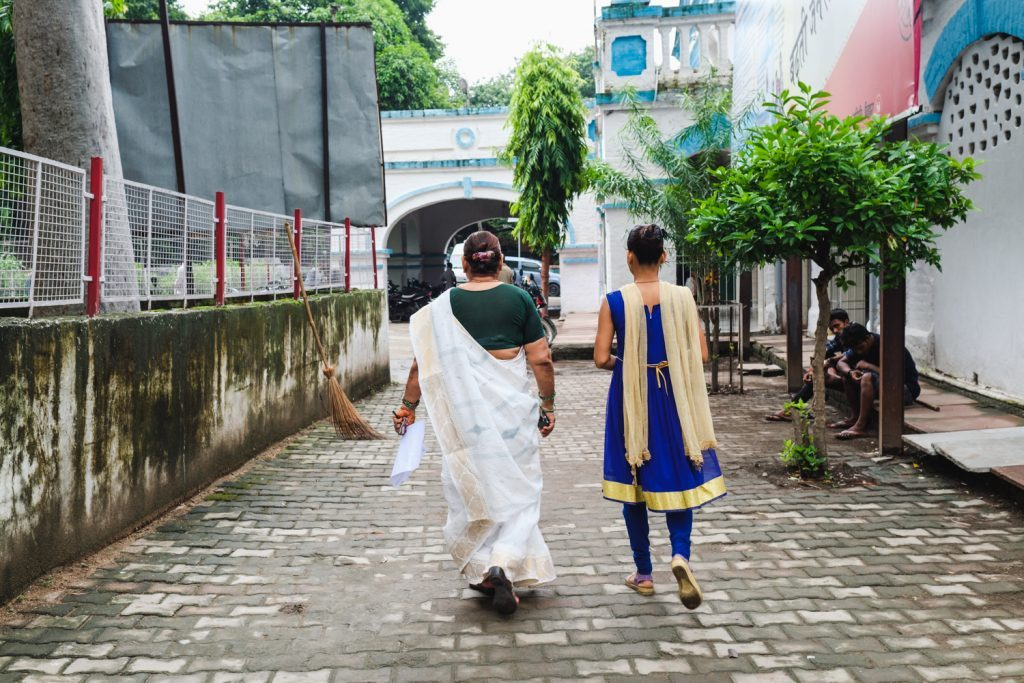 Two women are walking on a street. Their backs are turned against the camera.