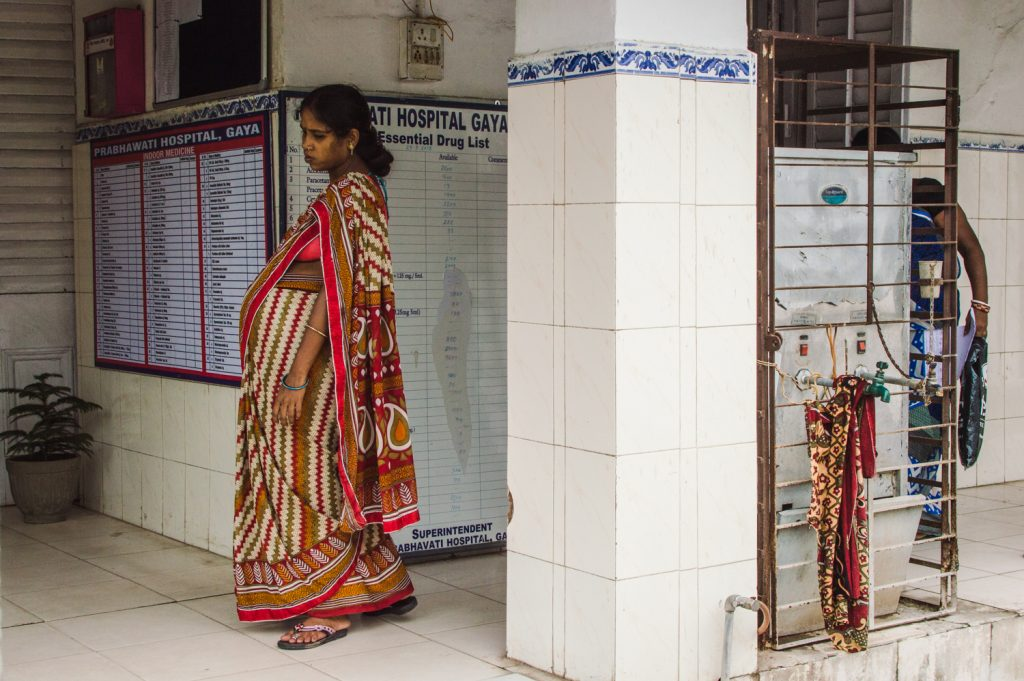Core aims to strengthen women's reproductive health access and outcomes. A heavily pregnant woman standing in the middle of a hospital waiting room wearing a colourful sari.