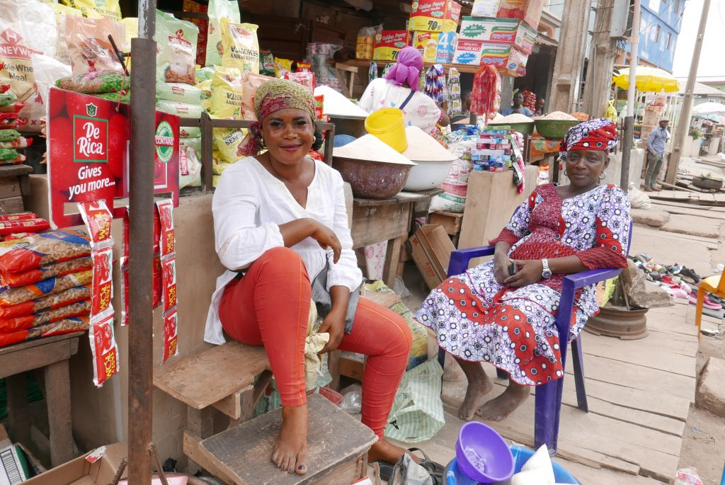 Two Nigerian women sitting on the market place. One is wearing a wax printed purple and red patterned dress and headgear, the other one red jeans and a white shirt.