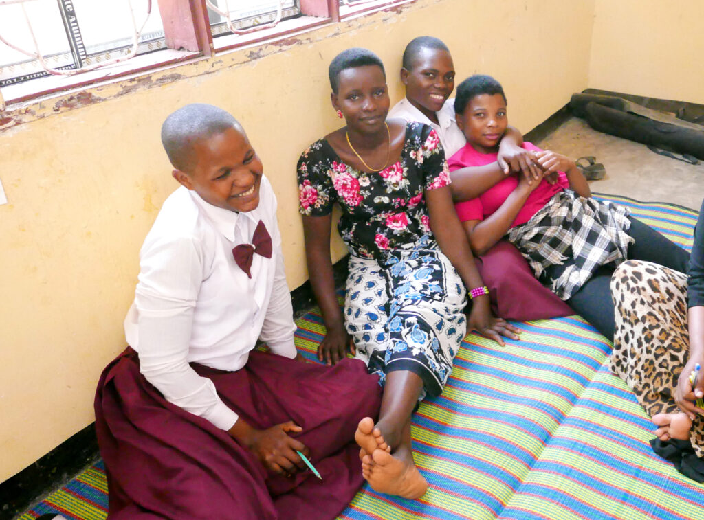 Four adolescent girls smiling. They are lying on a mattress leaning against a wall and hugging each other.