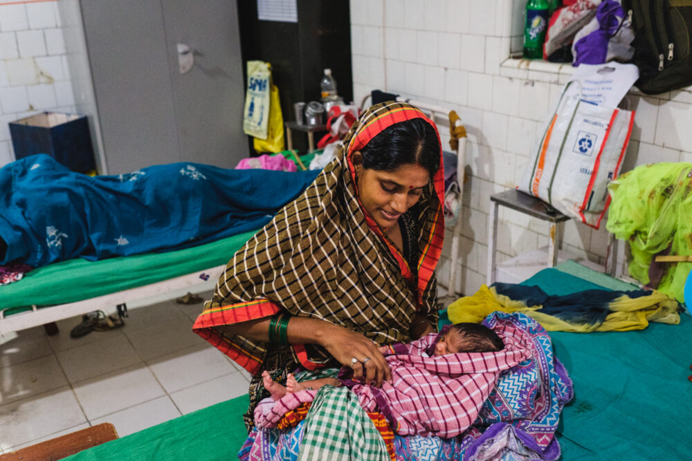 A young mother is attending to her newborn baby on a hospital bed. She is wearing a colourful sari and the baby is wrapped in a pink, checkered blanket.