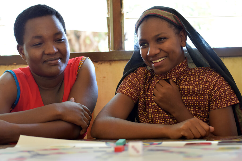 Two adolescent girls are discussing menstruation. They are playing a board game that helps them guide through their experience.