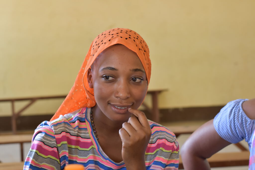 A young woman looking thoughtful. She is wearing a colourful, striped t-shirt and an orange scarf to cover her hair.