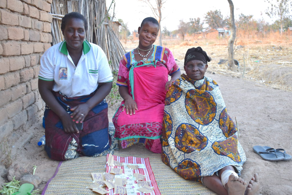 An adolescent girl with her mother and grandmother are discussing matters related to womanhood. In front of them is a paper where they have their life-course.