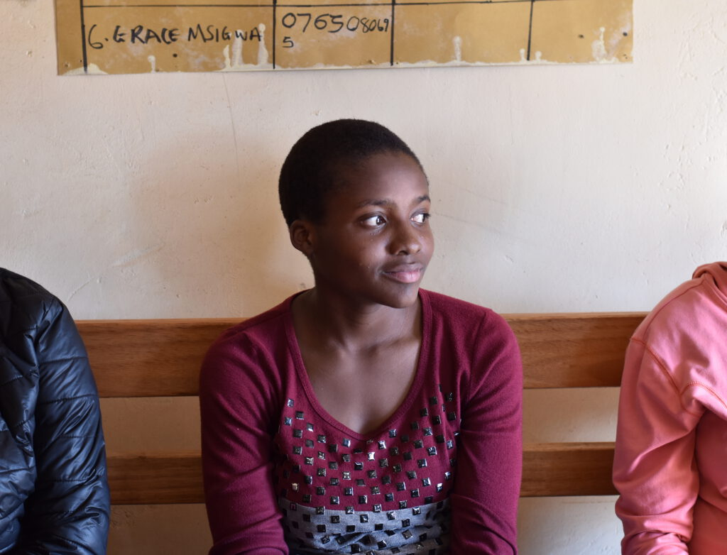 An adolescent girl sits on a bench in a healthcare centre looking sideways.
