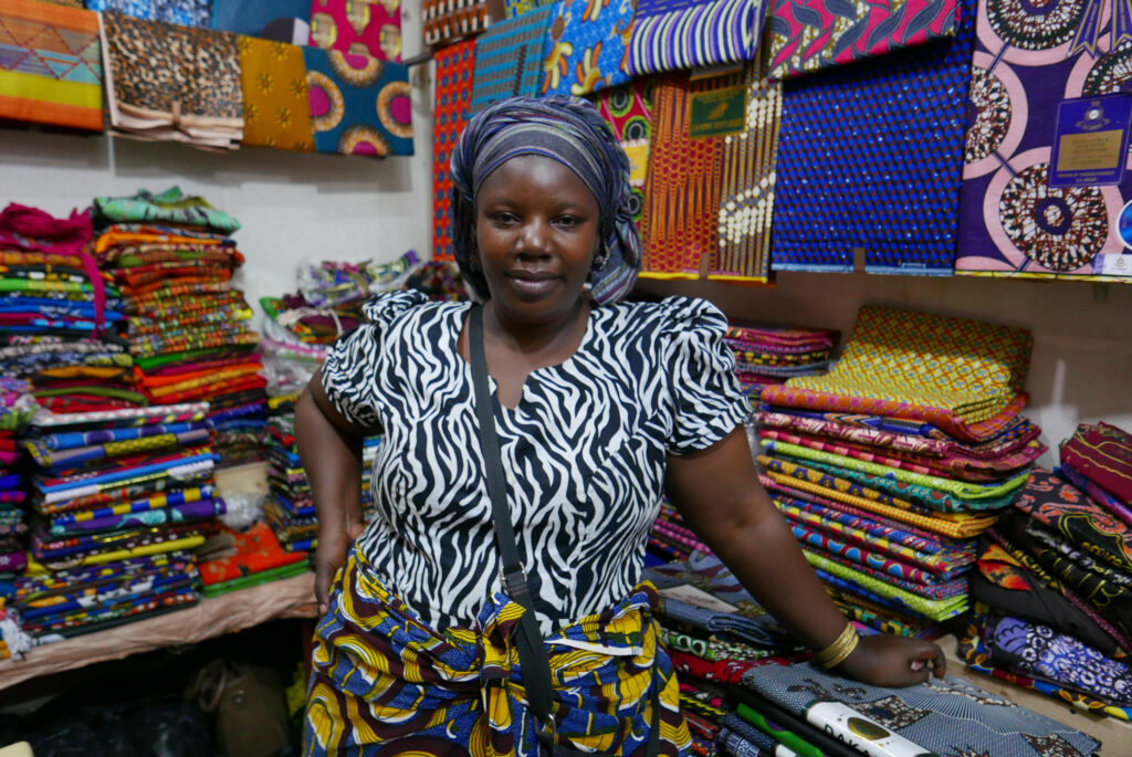 A young woman wearing colourful wax-printed shirt and skirt and a striped turban standing in a fabric store. She is surrounded by packs of wax-printed kitenge fabric.
