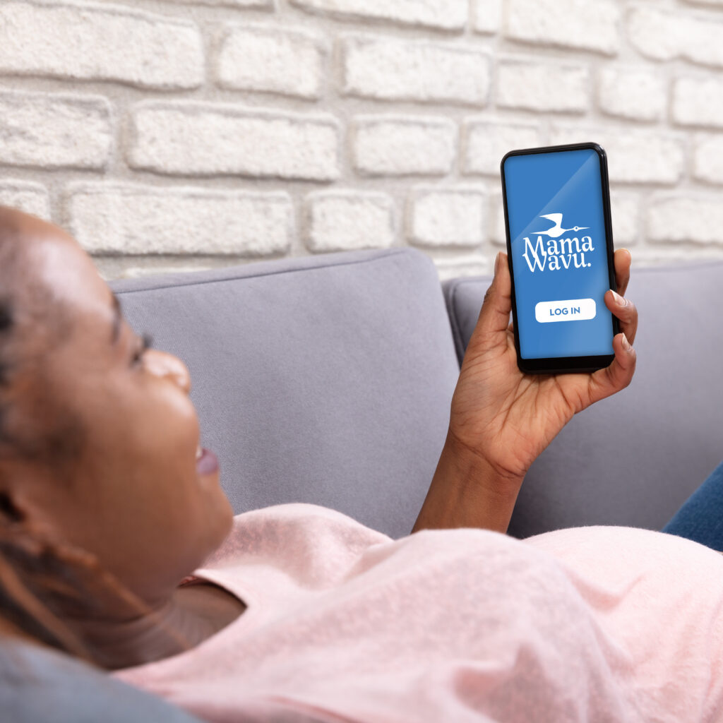 Pregnant woman lying on couch using Mama Wavu phone app