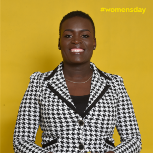 Editar Ochieng stands smiling broadly against a yellow background wearing a black and white houndstooth-patterned blazer.