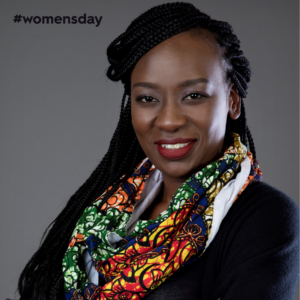 Scheaffer Okore smiles kindly in a colourful wax-printed scarf and a black shirt against a grey background.