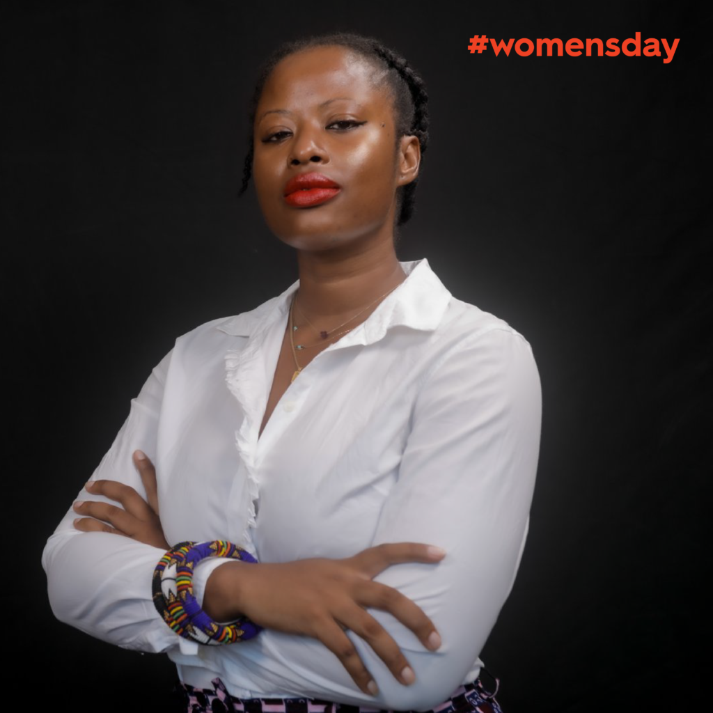 Vickie Remoe standing with a determined look and arms crossed in a white shirt against black background. Red text reads Women's Day 2020.