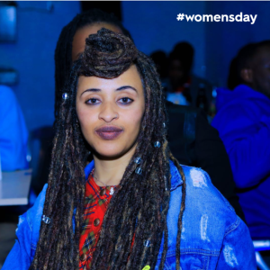 Zemdena Abebe looks defiantly at camera in long, beaded dreadlocks, wearing a ripped, blue jeans jacket and a red patterned shirt against a blue background.