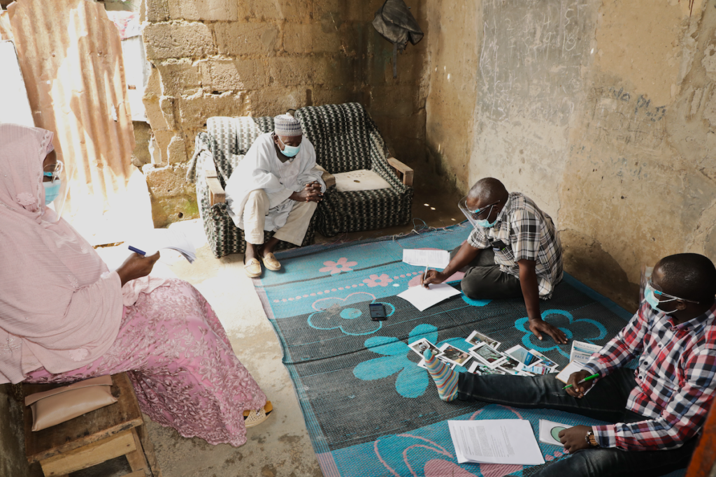 Men participating in Core Nigeria's design process. An elderly man sits on a couch, giving instructions to two men sitting on a mat on the floor where cards are being scattered.