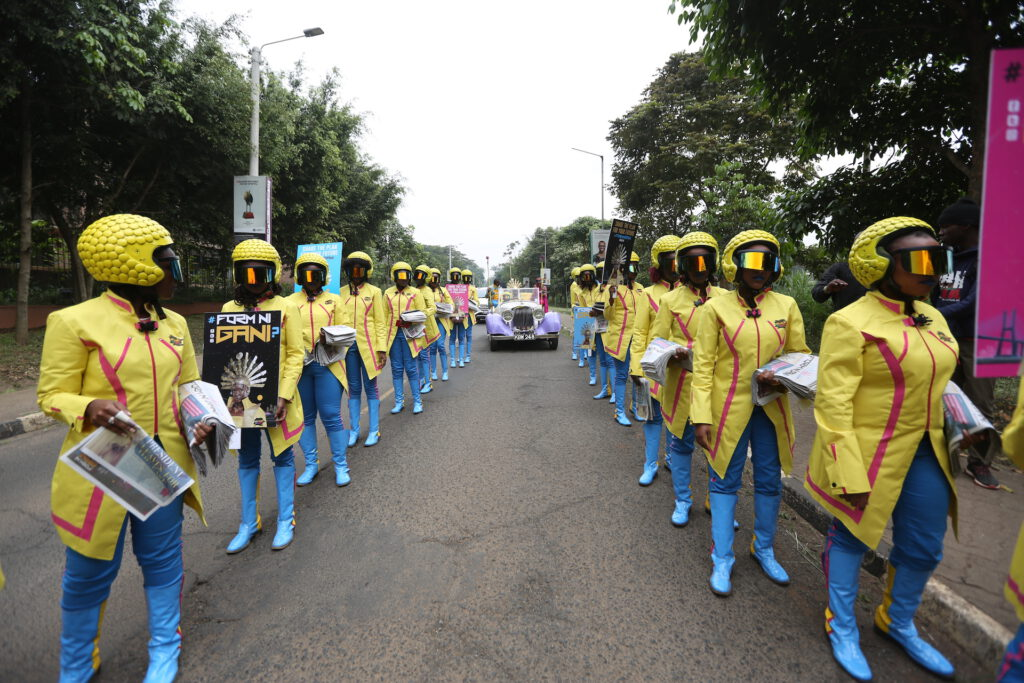 #FormNiGani time warriors clad in yellow futuristic clothing are standing at the side of a road handing out newspapers from Kenya in 2063 and welcoming the future female president in her car.