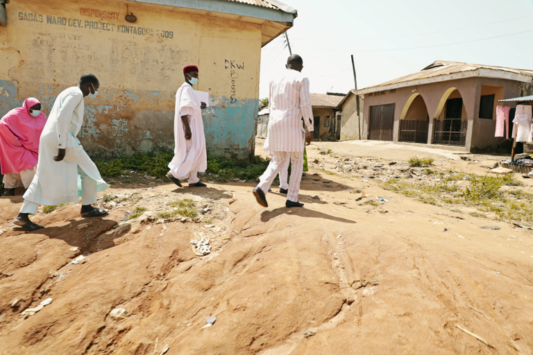 Four people, three men in light-coloured clothing and a woman in a pink burkha climb up a small hill to access the yard leading to the health centre.