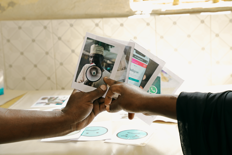 Design Clinic participant is holding four pictures of different communication channels. Another person is pointing a picture of a person speaking into a megaphone. Other pictures depict Instagram and WhatsApp. The fourth one is not visible.