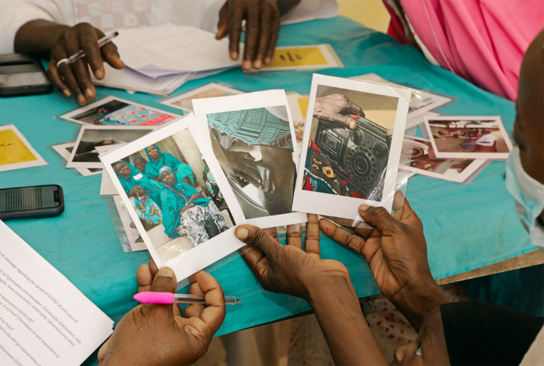 Two community leaders in Niger state hold three different photos in their hands depicting a group of people, a cell phone, and a radio.