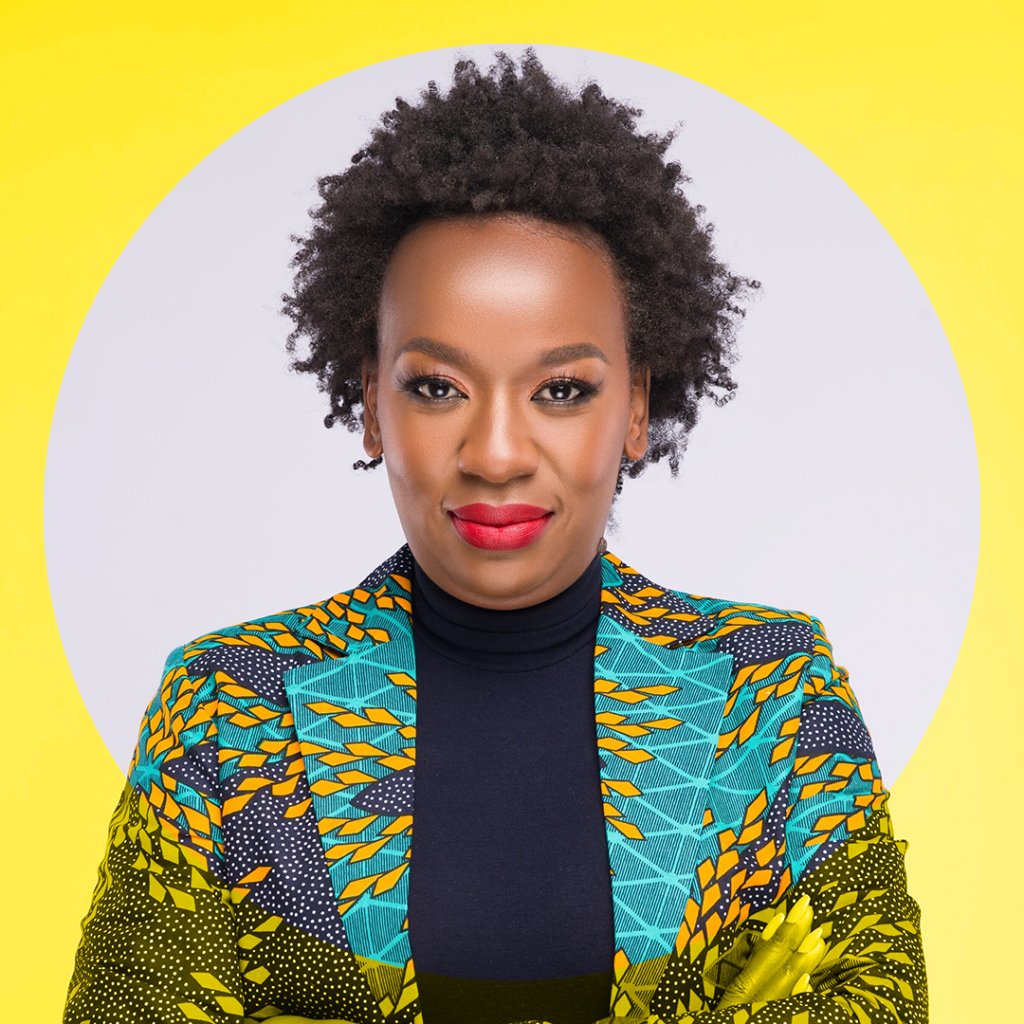 Portrait of Scheaffer Okore in a colourful, wax printed blazer against a yellow background.