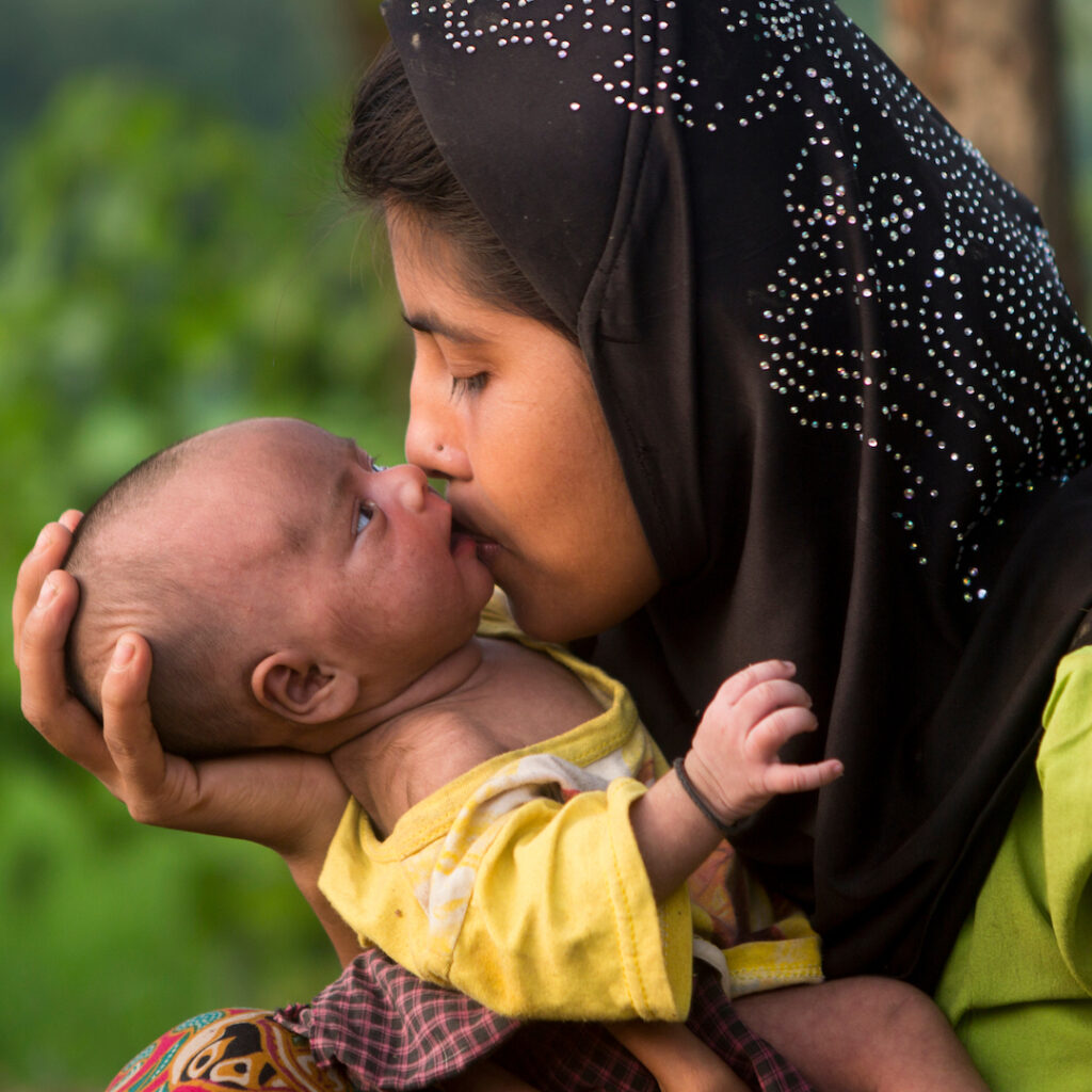 A Bangladeshi woman is holding her newborn baby in her arms, kissing the baby's cheek affectionately.
