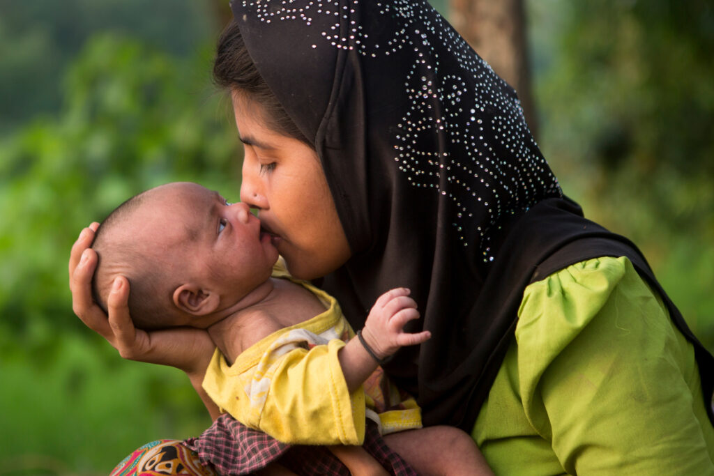 Healthy Women, Healthy Families seeks to bridge antenatal care seamlessly to postnatal care. A Bangladeshi woman is holding her newborn baby in her arms, kissing the baby's cheek affectionately.