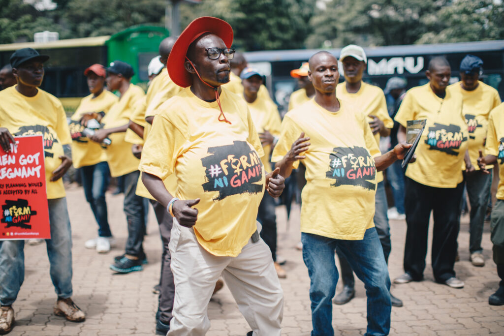 Pregnant men taking part in the social mobilisation event wearing yellow #FormNiGani t-shirts and fake bellies.
