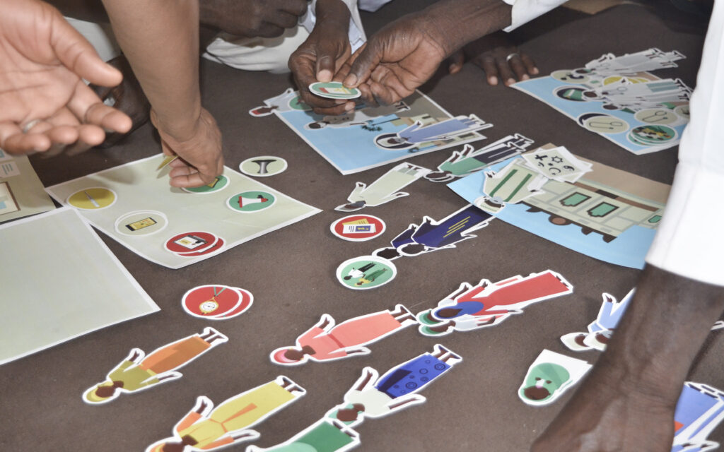 In prototyping, paper dolls depicting community members, objects depicting different means of communication and emotions, and cards depicting houses and other public settings are placed on the floor. Around them, hands are picking up different prompts to assist in the storytelling.