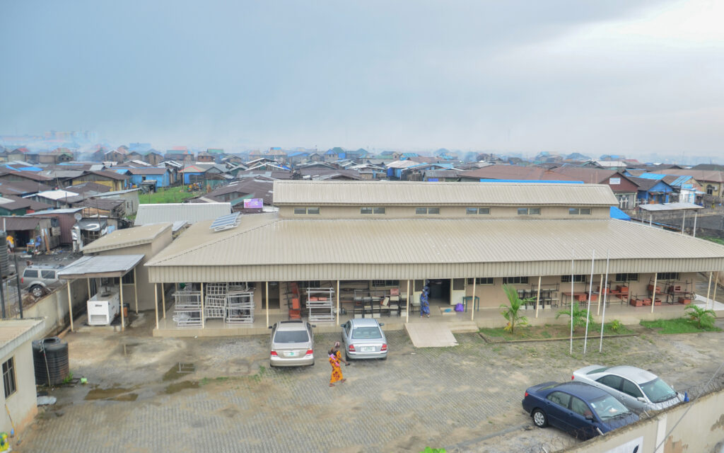 A view of the inner yard of the health centre located within the informal settlement. A woman is walking with a baby on her back on the yard. The yard is empty apart from four parked cars.