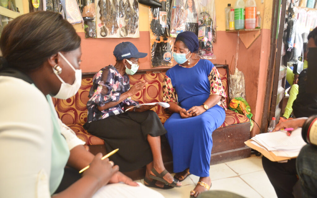 Two people are sitting on a sofa in a hair salon, one is a Lagos state team member and the other is the hair salon owner. Bags of brown and black hair extensions are hanging on the wall behind them. In the front, two women are listening to the interview, writing notes.