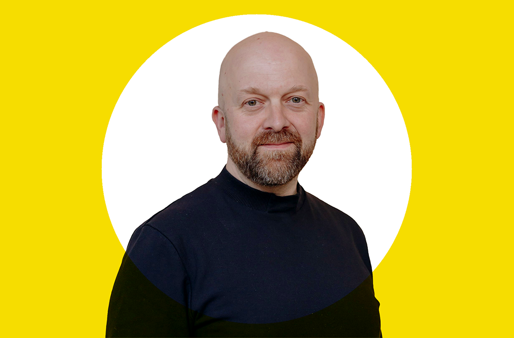 Scope's chief executive Simon Smith in a black polo shirt against a bright yellow background.