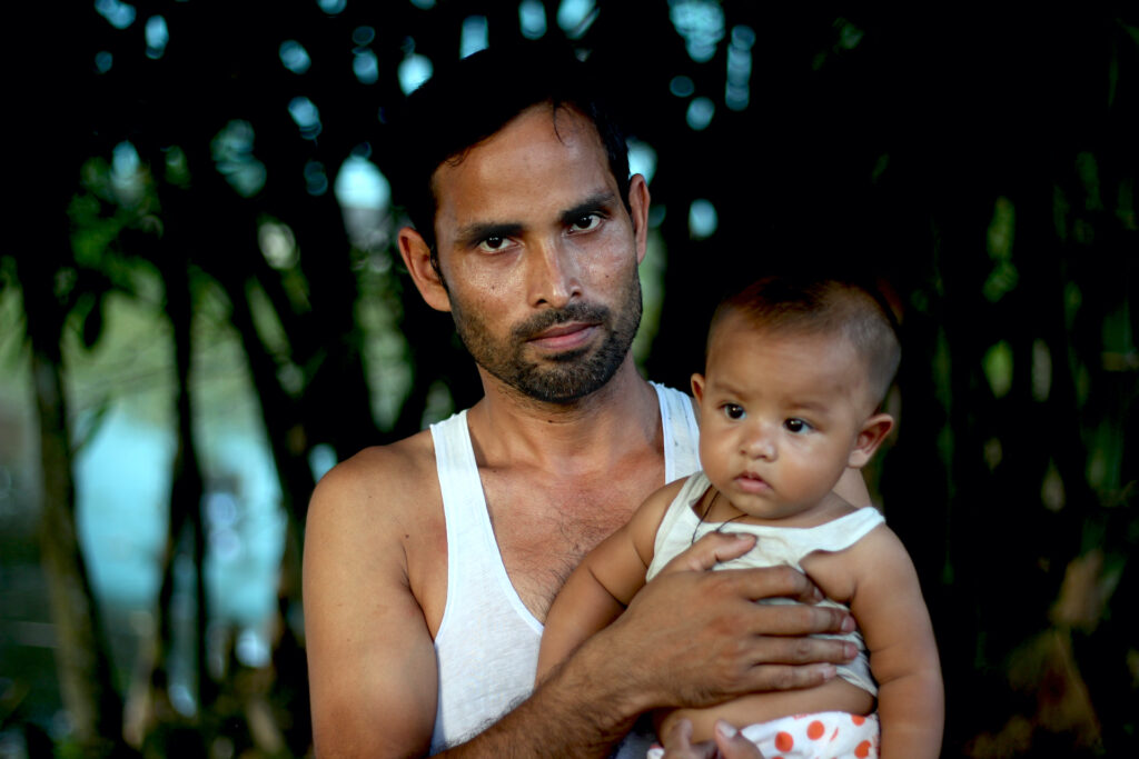 Group perinatal care modeling hopes to involve also young parents. A Bangladeshi father holding a baby in his lap.
