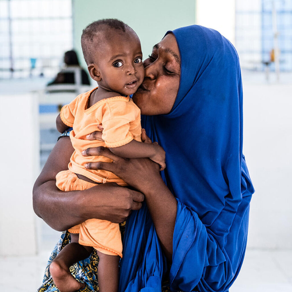 An Ethiopian woman holding her baby in a modern, light-filled maternity ward